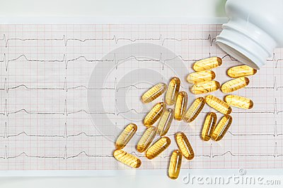 Fish oil capsules on cardiogram ECG, healthy heart concept