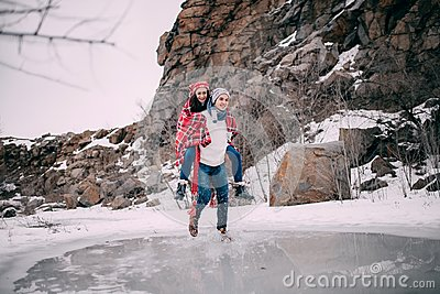Young man carries his girlfriend on back across puddle of melted water. Couple laughs.
