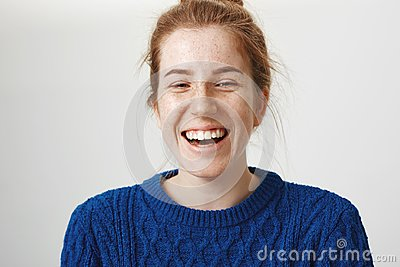 Close-up shot of emotive charming woman with red hair and cute freckles laughing out loud enjoying every day of youth