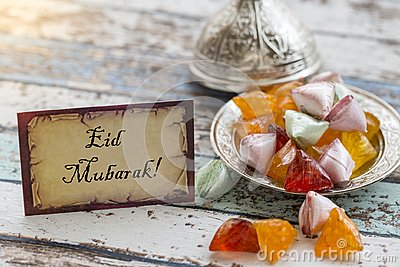 Eid mubarak text on greeting card on vintage table with candies