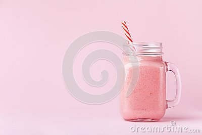 stock image of strawberry smoothie or milkshake in mason jar on pink pastel background. healthy food for breakfast and snack.