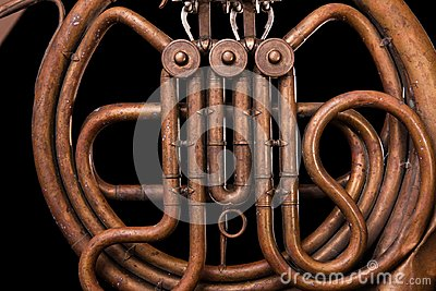Vintage bronze pipes, valve, key mechanical elements french horn, black background. Good pattern, prompt music instrument.