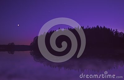 Beautiful purple sunset by lake in summer, with moon shining.