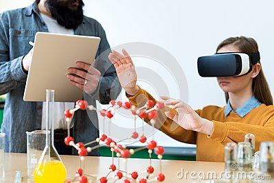 Young teacher using Virtual Reality Glasses and 3D presentation to teach students in chemistry class. Education, VR, Tutoring.