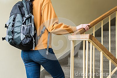 Young unrecognisable depressed lonely female college student walking up the stairs at her school.