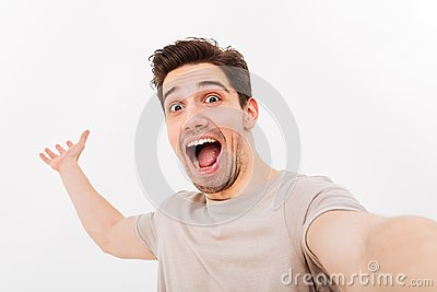 Photo of excited man in casual t-shirt and bristle on face screaming in happiness while taking selfie, isolated over white