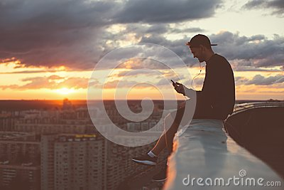 Young brave man sitting on the edge of the roof with smartphone