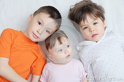Happy kids, three children different ages lying, portrait of boy, little girl and baby girl, happiness in childhood of siblings