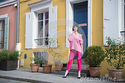 Woman stand in high heel shoes in paris, france, vacation. Woman in pink sweater, trousers on street, fashion. Beauty, look, makeu