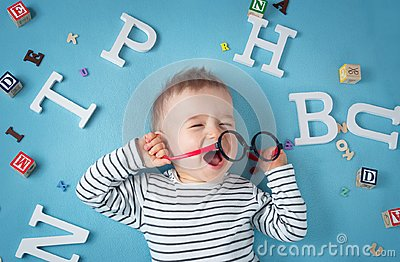 One year old child lying with spectacles and letters