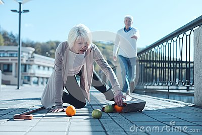 Scared woman dropping groceries while falling to ground