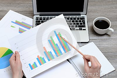 Worker looking at graphics. Top view on hands holding graphs, laptop, cup of coffee, workplace workstation, project progress best
