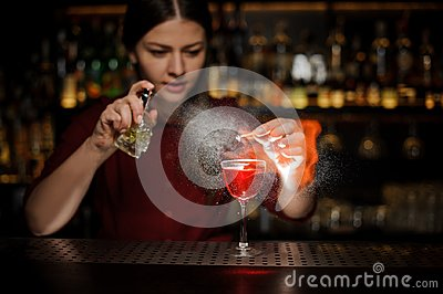 Female bartender sprinkling a cocktail glass with Aperol syringe cocktail with a peated whisky and making a smoky note on the bar