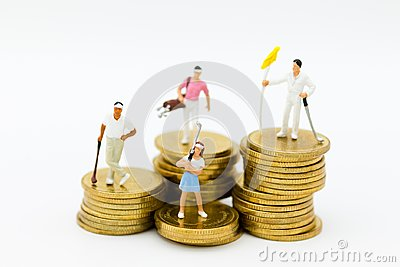 stock image of miniature people: golfers standing on coins. image use for . image use for sport,activities , hobbies concept