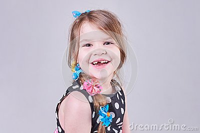 Beautiful little girl smiles a toothless smile