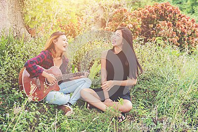 stock image of young teenage looking at her female friend while playing guitar,relaxing time enjoyment.