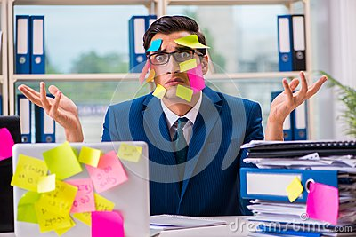 The businessman with reminder notes in multitasking concept