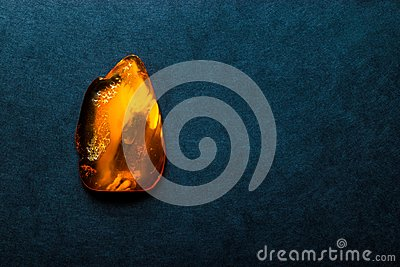 Amber Stone on Dark Blue Background Surface With Free Space