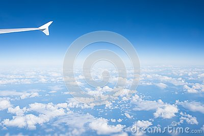 Sky and clouds seen from plane window. Atmosphere, stratosphere, air. Cloudscape, weather, nature. Wanderlust, adventure, discover