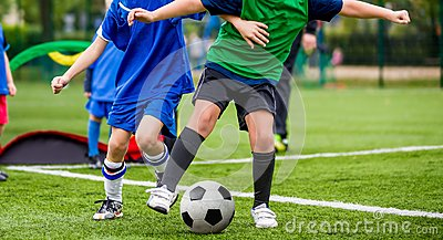 Children play sports. Kids kicking football match. Young boys playing soccer on the green grass pitch. Youth sports competiton.