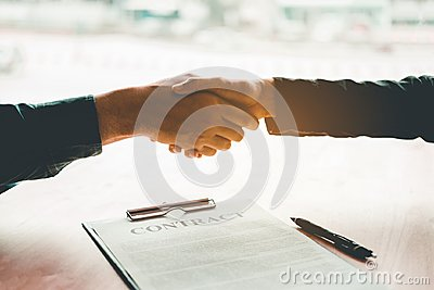 Business people negotiating a contract handshake between two col