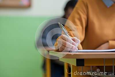 Students taking exam in classroom. Education test.
