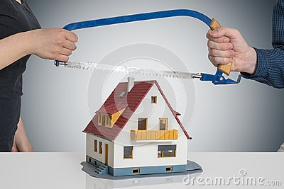 Divorce and dividing a house concept. Man and woman are splitting model of house with saw