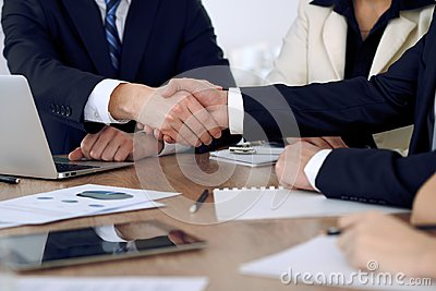 Close up of business people shaking hands at meeting or negotiation in the office. Partners are satisfied because