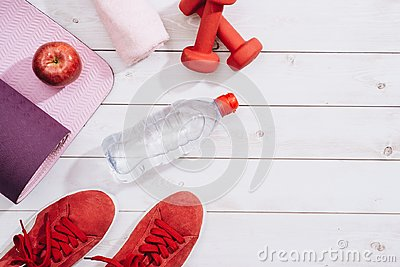 Fitness, healthy and active lifestyles Concept, dumbbells, sport shoes, bottle of waters and apple on wood background.