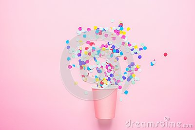 Drinking Paper Cup with Multicolored Confetti Scattered on Fuchsia Background. Flat Lay Composition. Birthday Party Celebration