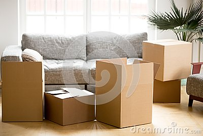 Cardboard carton boxes in living room, packing and moving concep