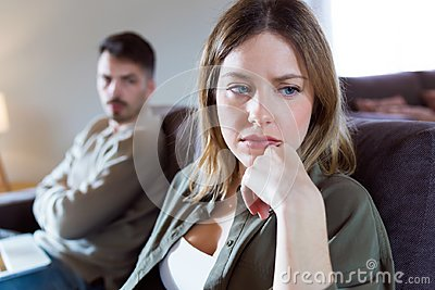 stock image of offended young woman ignoring her angry partner sitting behind her on the couch at home.