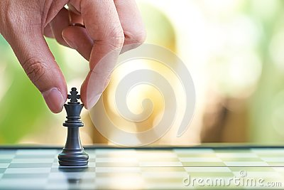 Businessman holding a King Chess is placed on a chessboard.using as background business concept and Strategy concept with copy spa