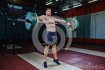 Muscular fitness man preparing to deadlift a barbell over his head in modern fitness center.Functional training.Snatch