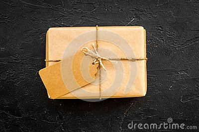 Parcel packaging box wrapped with craft paper with empty label mockup on black background top view copy space