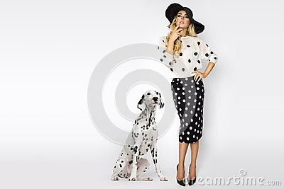 Beautiful, blonde woman in elegant polka dots and a hat, standing on a white background next to a dalmatian dog