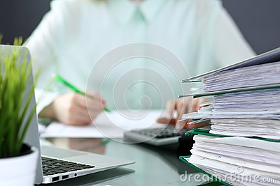Bookkeeper or financial inspector making report, calculating or checking balance. Binders with papers closeup. Audit an