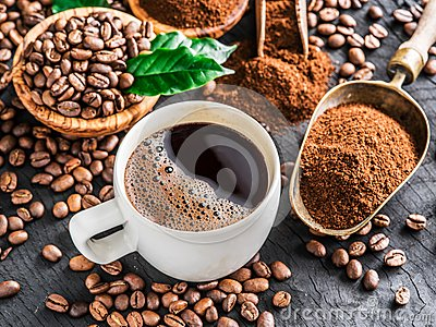 Roasted coffee beans, ground coffee and cup of coffee on wooden