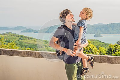 Dad and son in the background of Tropical beach landscape panorama. Beautiful turquoise ocean waives with boats and sandy coastlin