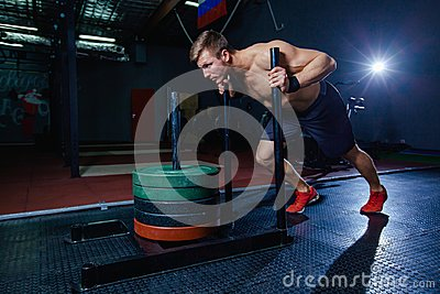 Sled push man pushing weights workout exercise at gym. Cross fit style