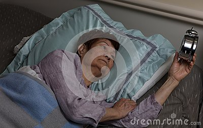 Restless senior woman glaring at alarm clock during nighttime while in bed