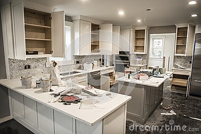 Messy home kitchen during remodeling with cabinet doors open cluttered with paint cans, tools and dirty rags, canned ceiling light