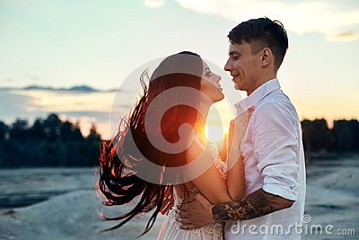 Love kiss and hugs in love couples at sunset in the evening sun, a walk through the mountains and hills. Sensual and gentle loving