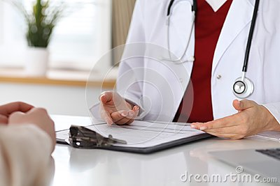 Close up of a doctor and patient hands while discussing medical records after health examination