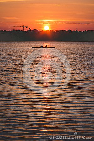 Silhouette of Team work oft two young men in a row boat at sunset