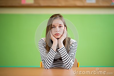 Sad student sitting in classroom with her head in hands. Education, high school, bullying, pressure, depression.