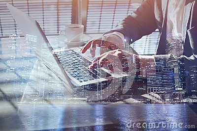Double exposure of business man working online on laptop computer, close up of hands