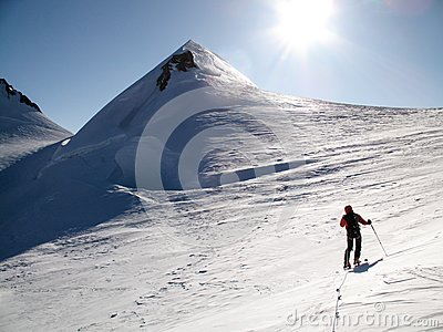 Male back country skier on a ski toru on his way to a high alpine summit in the Monte Rosa mountains on a huge glacier