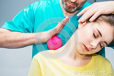 Woman at the physiotherapy receiving ball massage from therapist. A chiropractor treats patient`s shoulder, neck in medical offic