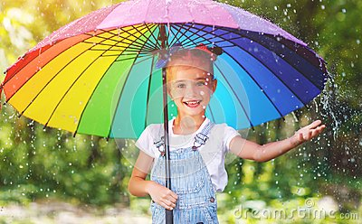Happy child girl laughs and plays under summer rain with an umbr